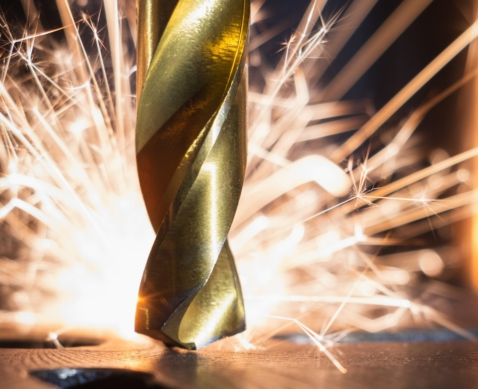 industrial drill bit with sparks in the distance